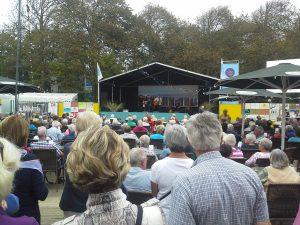 Menschen sitzen vor Veranstaltungsbühne in Domburg