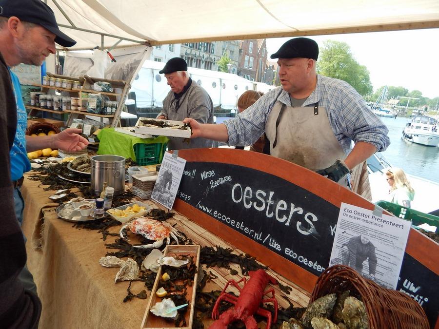Austernverkäufer reicht Ware über Marktstand in Veere