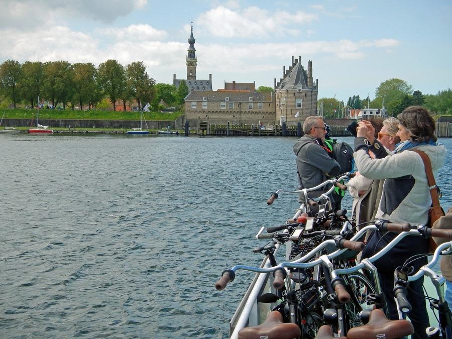 Passagiere auf Fahrradfähre vor der Kulisse vn Veere auf dem Veerse Meer