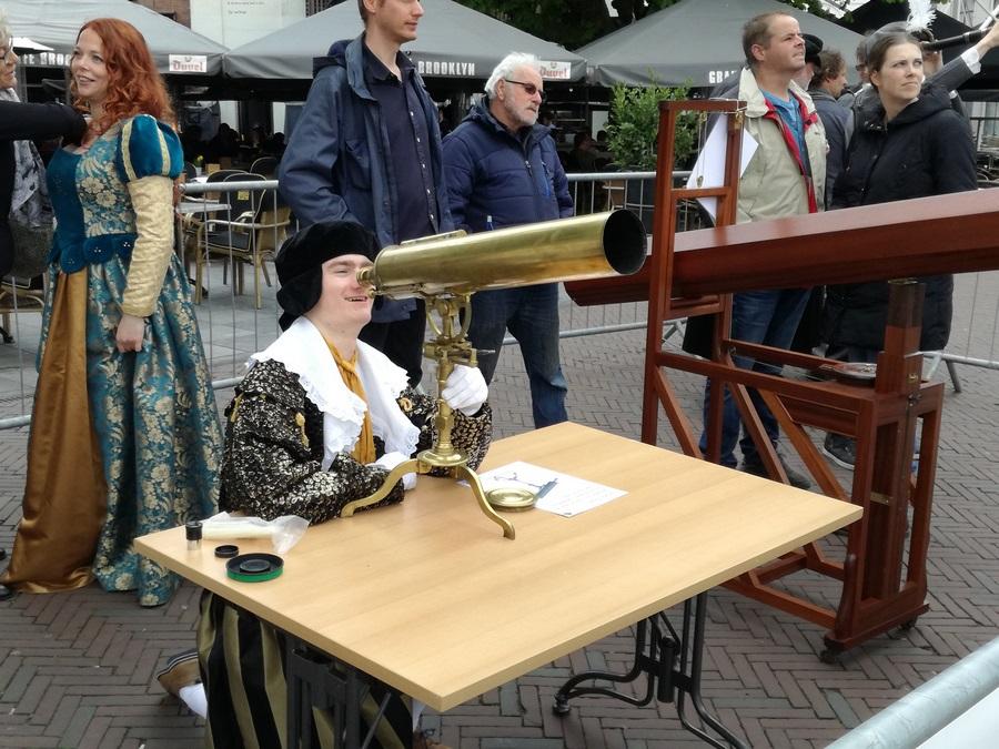 Schauspieler in historischer Tracht am antiken Fernrohr auf Markt in Middelburg